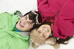 Overhead View Of Two Teenagers On Ski Holiday In Mountains - stock photo