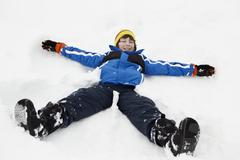 Young Boy Making Snow Angel On Slope - stock photo