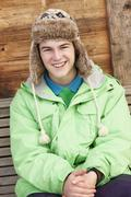 Teenage Boy Dressed For Cold Weather Sitting On Wooden Bench - stock photo