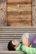 Teenage Boy With Snowboard On Ski Holiday Lying On Wooden Bench - stock photo