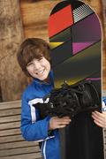 Boy With Snowboard On Ski Holiday In Front Of Wooden Background Stock Photos