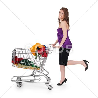 Stock photo of Smiling girl with shopping cart buying colorful clothing