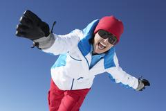 Woman Having Fun On Ski Holiday In Mountains - stock photo