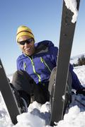 Male Skier Sitting In Snow With After Fall - stock photo