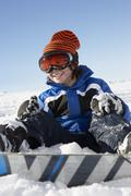 Young Boy Sitting In Snow With Snowboard Stock Photos