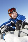 Nuori poika istuu lumen Snowboard Kuvituskuvat