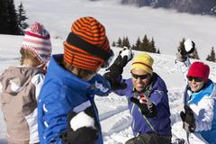 Family Having Snowball Fight On Ski Holiday In Mountains Stock Photos