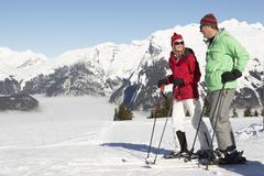 Couple Having Fun On Ski Holiday In Mountains Stock Photos