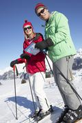Couple Looking At Map Whilst On Ski Holiday In Mountains Stock Photos