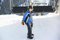 Young Boy Getting Off chair Lift On Ski Holiday In Mountains - stock photo