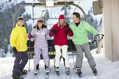 Teenage Family Getting Off chair Lift On Ski Holiday In Mountains - stock photo
