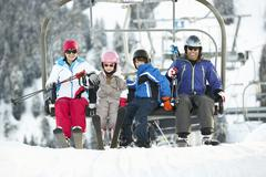 Family Getting Off chair Lift On Ski Holiday In Mountains - stock photo