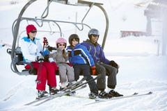 Family Getting Off chair Lift On Ski Holiday In Mountains Stock Photos