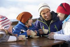 Family Enjoying Hot Drink In Caf̩ At Ski Resort - stock photo