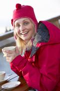 Woman Enjoying Hot Drink In Caf̩ At Ski Resort - stock photo