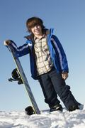 Young Boy With Snowboard On Ski Holiday In Mountains Stock Photos