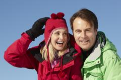 Couple Standing In Snow Wearing Warm Clothes On Ski Holiday In Mountains Stock Photos