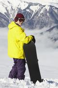 Stock Photo of Teenage Snowboarder Admiring Mountain View Whilst On Ski Holiday In Mountains