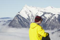 Teenage Snowboarder Admiring Mountain View Whilst On Ski Holiday In Mountains Stock Photos