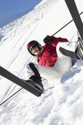 Female Skier Sitting In Snow With After Fall - stock photo