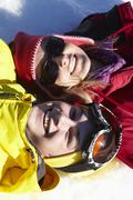 Overhead View Of Mother And Teenage Son Lying In Snow On Ski Holiday In Stock Photos