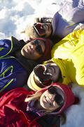 Overhead View Of Teenage Family Lying In Snow On Ski Holiday In Mountains - stock photo