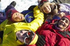 Stock Photo of Overhead View Of Teenage Family Lying In Snow On Ski Holiday In Mountains