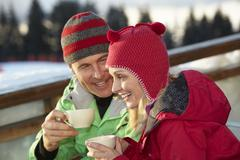 Stock Photo of Couple Enjoying Hot Drink In Caf̩ At Ski Resort
