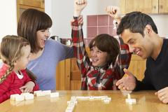 Family Playing Dominoes In Kitchen Stock Photos