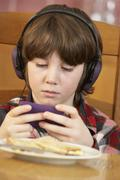 Boy Playing With Hand Held Games Console Whilst Eating Breakfast Stock Photos