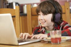Boy Using Laptop Whilst Eating Breakfast Stock Photos