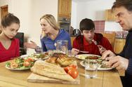 Stock Photo of Teenage Family Having Argument Whilst Eating Lunch Together In Kitchen