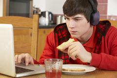Teenage Boy Using Laptop Whilst Eating Breakfast - stock photo