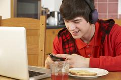 Teenage Boy Using Laptop And Listening To MP3 Player Whilst Eating Breakfast - stock photo