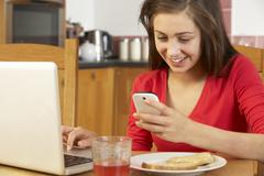 Teenage Girl Using Laptop And Mobile Phone Whilst Eating Breakfast Stock Photos