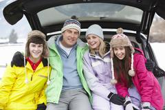 Teenage Family Sitting In Boot Of Car Wearing Winter Clothes Stock Photos