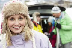 Mother Smiling At Camera Whilst Family Load Skis In Boot Of Car Stock Photos