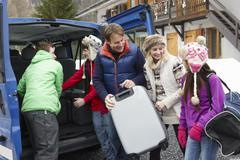 Family Unloading Luggage From Transfer Van Outside Chalet On Ski Holiday Stock Photos