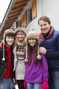Stock Photo of Portrait Of Family Standing Outside Chalet On Ski Holiday