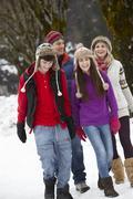 Teenage Family Walking Along Snowy Street In Ski Resort Stock Photos