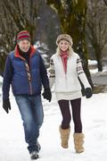 Couple Walking Along Snowy Street In Ski Resort Stock Photos