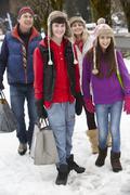 Teenage Family Carrying Shopping Walking Along Snowy Street - stock photo