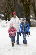Mother Walking Two Children To School Along Snowy Street In Ski Resort - stock photo