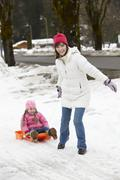Mother Pulling Daughter On Sledge Along Snowy Street In Ski Resort - stock photo