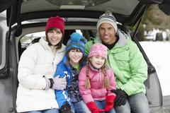 Family Sitting In Boot Of Car Wearing Winter Clothes - stock photo