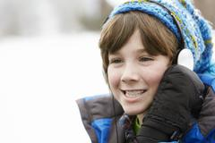 Boy Wearing Headphones And Listening To Music Wearing Winter Clothes In Snowy - stock photo