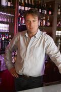 Portrait Of Barman Standing Behind Bar - stock photo