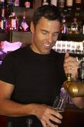 Portrait Of Barman Standing Behind Bar Pouring Beer - stock photo