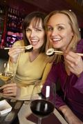 Two Women Enjoying Sushi In Restaurant - stock photo