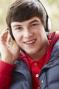 Teenage Boy Wearing Headphones And Listening To Music Wearing Winter Clothes Stock Photos